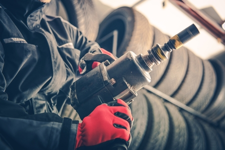 Seasonal Car Servicing Concept Photo. Auto Mechanic with Rotated Pneumatic Gun in Hands Are Ready For the Job. Automotive Industry.