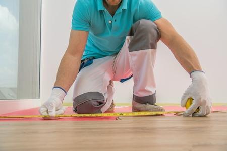 Installing New Hardwood Floor Panels by Professional Installer. Home Interior Remodeling. Construction Theme.