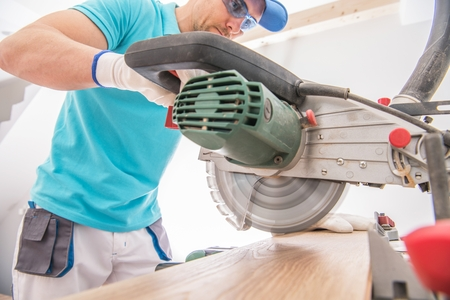 Circular Saw Cutting Job. Contractor Worker and the Power Tool. Remodeling Theme.