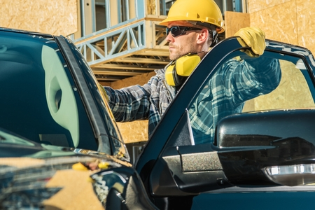 Construction Business Owner. Caucasian Supervisor in His 30s Wearing Yellow Hard Hat and His Company Pickup Truck.