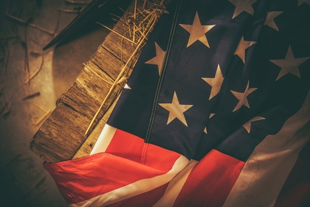 Vintage American Flag Laying on the Aged Wooden Crate. Closeup Photo. United States of America National Flag. Standard-Bild