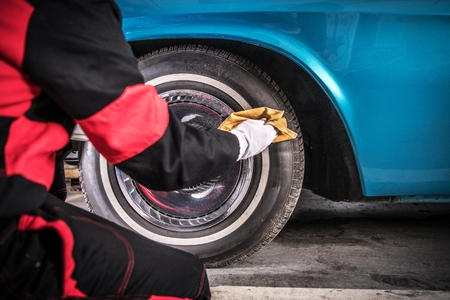 Classic Car Wheels Care. Professional Automotive Worker Cleaning Tire Using Specialized Spray. Foto de archivo - 121633645