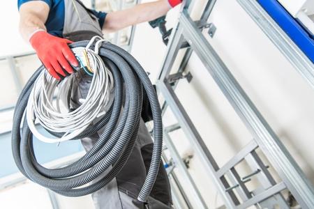 Bouwvakker voorbereiding van elektrische systeeminstallatie in het onlangs gerenoveerde huis. Stockfoto