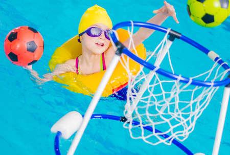Swimming Pool Fun Time. Caucasian Nine Years Old Girl Playing Ball Inside the Pool. Imagens