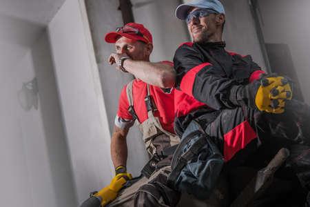 Construction Site Crew. Two Caucasian Workers Taking Short Break. Industrial Theme. Imagens