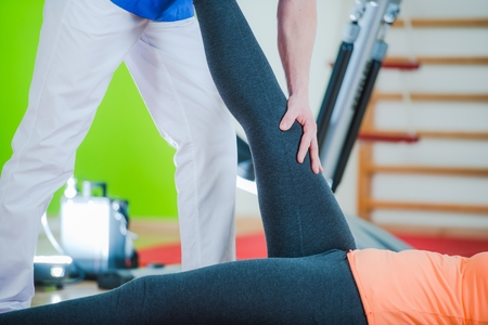 Rehabilitation Physiotherapy. Caucasian Therapist Working with Patient. Closeup Photo. Stock Photo