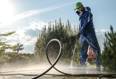Mantenimiento de lavado de jardines. Trabajador caucásico de unos 30 años con lavadora a presión limpiando caminos de ladrillos.
