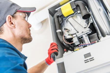 Technicien et le problème de chauffage. Travailleur caucasien regardant à l'intérieur du chauffage central au gaz essayant de résoudre le problème.