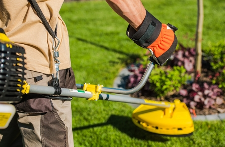 Caucasian Gardener with Gasoline Brush Cutter and String Trimmer on His Shoulder. Trimming Garden Grass. Landscape Maintenance.