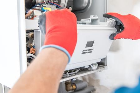 Professionele technicus reparatie centrale gaskachel. Close-up foto. Huishoudelijke verwarmingsapparatuur. Stockfoto