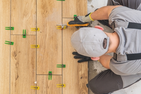 Professional Remodeling Worker Installing Wooden Like Ceramic Floor in the Kitchen Area. Home Renovation Project.