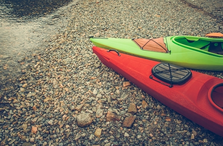 Summer Trip with Kayaks. Two Canoes on the Rocky Lake Shore. Water Sports Theme.