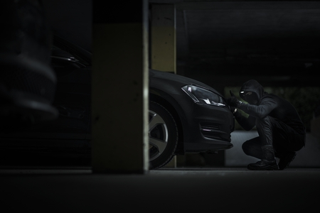 Caucasian Car Thief on a Parking Lot Trying to Open Modern Compact Car Hood to Get Access to Alarm Device.