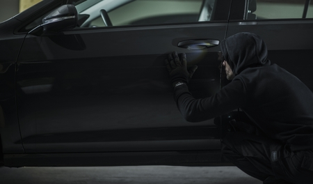 Men in Black Hood Stealing Modern Vehicle. Car Theft Concept Photo. 版權商用圖片
