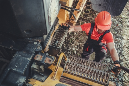 Heavy Duty Machinery Operator Going Up on Metal Truck Ladder. Mine Truck Driving. Foto de archivo - 124765143