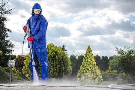 Hombres vestidos con abrigo húmedo industrial con lavadora a presión de limpieza de entrada.