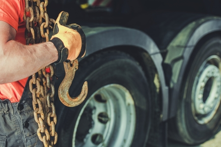 Trucker with Heavy Chains and Hook For Securing Cargo Load. Transportation Industry.