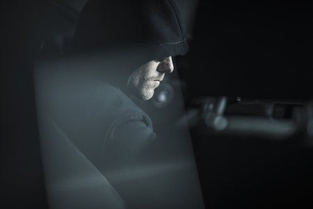 Caucasian Robber in Black Hood Waiting For a Good Moment Seating in a Car. Crime Concept Photo. Stok Fotoğraf