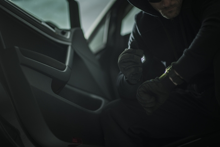 Suspicious Men with Small Flashlight in a Car. Vehicle Theft or Robbery Concept Photo.