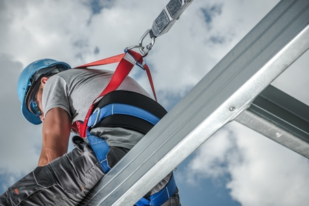Safety Harness Equipment. Caucasian Contractor in His 30s on a Steel Building Frame. Shock Absorbing Lanyard