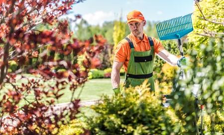 Agriculture Concept. Gardener with Rake. Summer Time Backyard Garden Maintenance.