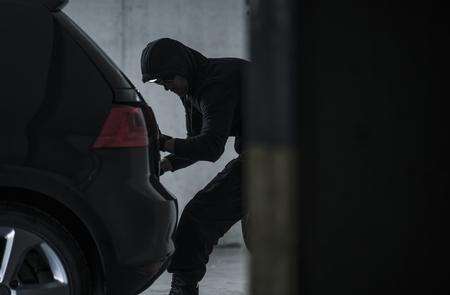 Masked Caucasian Car Thief Stealing Modern Vehicle. Transportation Theme. Stok Fotoğraf