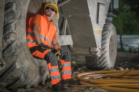 Caucasian Road Construction Worker in His 30s Taking Short Break and Relaxing Inside Heavy Equipment Wheel.