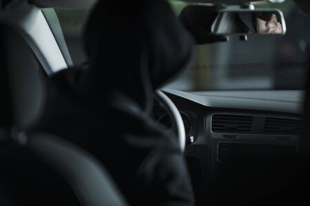 Grand Theft Auto Concept Photo with Caucasian Thief in His 30s Already Inside Stolen Car Taking Look in a Back Mirror. Automotive Theme. Stock Photo