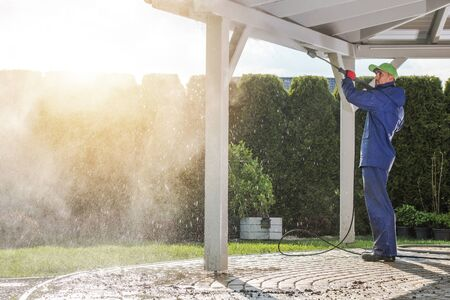 House Patio Roof Power Cleaning. Caucasian Worker with Pressure Washer. Standard-Bild
