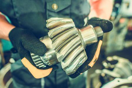 Machine Spare Part in Mechanic Hands. Closeup Photo. Repairing Heavy Duty Construction Machine. Industrial Theme. Big Fix. Stock Photo