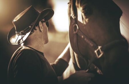 Caucasian Cowboy in His 60s with Horse in Equestrian Facility. Retirement Hobby.