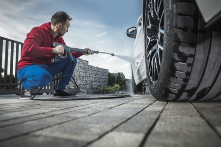 Caucasian Men Washing His Modern Car on a Driveway Using Pressure Washer.