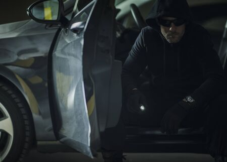 Caucasian Burglar with Flashlight in a Hood Seating Inside Modern Car. Thief Portrait. Imagens
