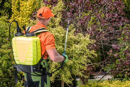 Garden and Agriculture Fertilization Technology. Caucasian Gardener with Pesticide Spraying Equipment.