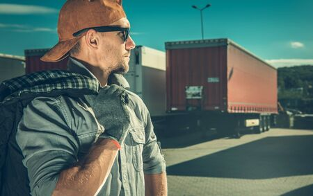 Profession Truck Driver. Caucasian Trucker in His 30s on a Truck Stop.
