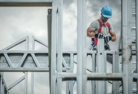 Construction Business Industry. Caucasian Skeleton Frame Worker in His 30s. Safety Harness.