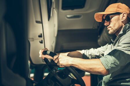 Transportation Industry. Caucasian Truck Driver Inside Vehicle Preparing For the Next Delivery Destination.
