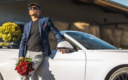 Dating Caucasian Senior in His 60s with Roses in Front of His Convertible Car.