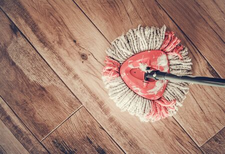 Cleaning Home Floor with Mop with Detergent. Ceramic Wooden Like Flooring.