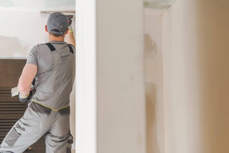 Caucasian Worker Finishing Home Walls. Home Improvements Theme. Imagens