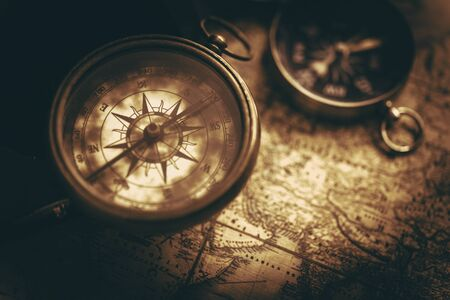 Aged Vintage Compass and World Map Closeup. Old School Sepia Color Grading. Adventure and Journey Theme. Imagens