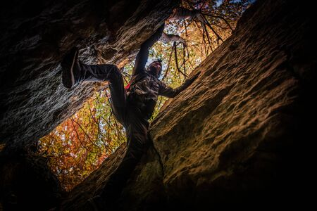 Extreme Cave Exploration by Caucasian Sportsman. Climbing Between Two Rock Walls. Imagens