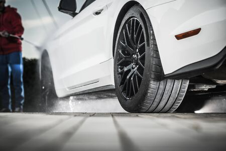 Self Car Washing on a Driveway. Cleaning Modern Vehicle. Automotive Theme. Imagens