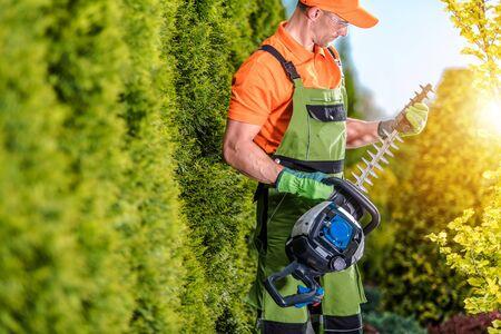 Caucasian Gardener with Garden Power Equipment. Gasoline Trimmer. Hedge Trimming Job.