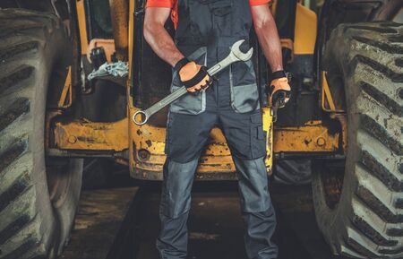 Industrial Mechanic Job. Caucasian Men with Metal Wrench in Front of Heavy Machine. Repair Shop Concept. Imagens