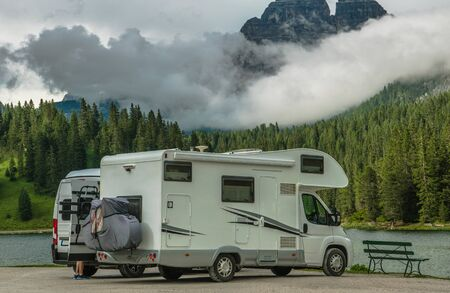 Scenic Camper Camping. Two Motorhomes on the Lake Shore. Scenic Cloudy Mountain Range in a Background. Recreational Vehicle Road Trip. Imagens