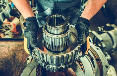 Heavy Duty Mechanic with Industrial Grade Vehicle Part in Hands.