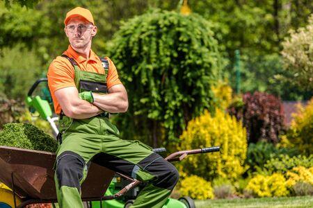 Professional Gardener Job. Satisfied Caucasian Garden Worker in His 30s Relaxing During Mid Day Work Break. Landscaping Industry.