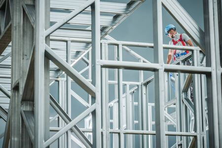 Caucasian Worker on the Skeleton Steel Building Construction. Industrial Theme. Imagens