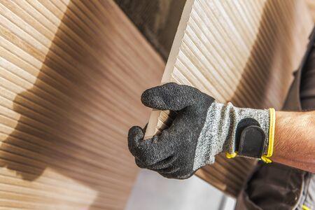 Ceramic Tiles Wall Install. Construction Worker Installing Modern Design Tile. Imagens